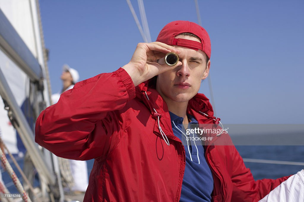 Young man looking through a telescope on a  sailing boat : Photo