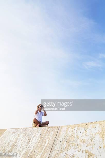 Young Man Looking Through Binocular