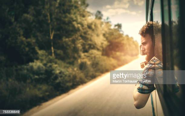 Young Man Looking Through Bus Window