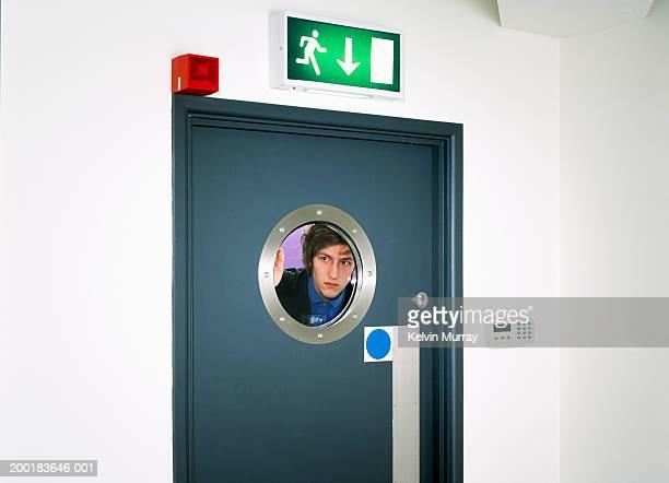 Young man looking through circular window on door, view through glass