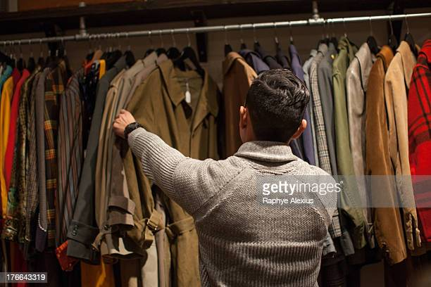 young man looking through clothes rail in vintage shop - coat stock pictures, royalty-free photos & images