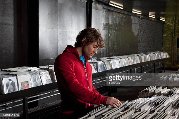 A young man looking through records at a record store