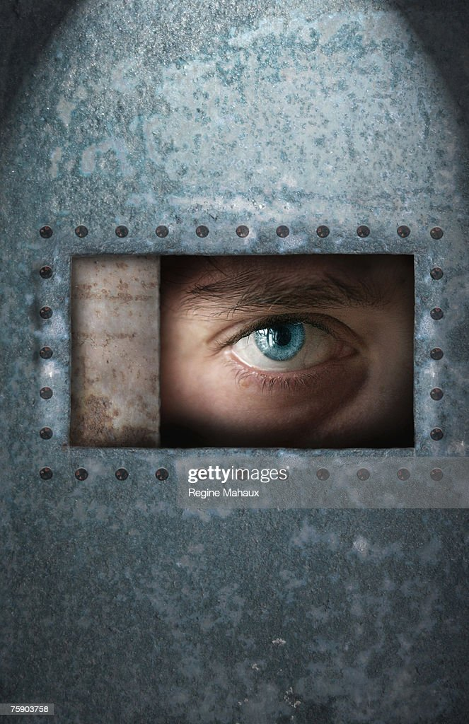 Young man looking through window in metal enclosure, close-up of eye : Stock Photo