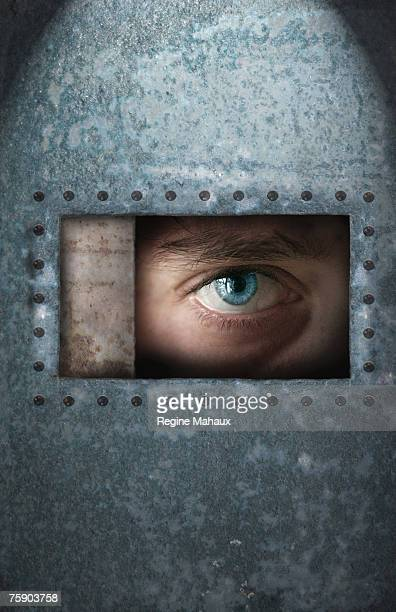 Young man looking through window in metal enclosure, close-up of eye