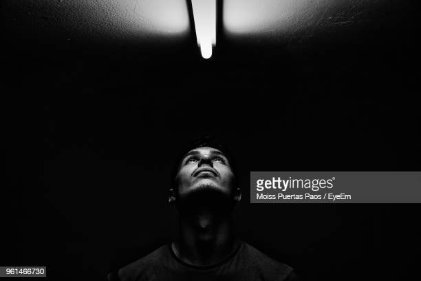 Young Man Looking Towards Fluorescent Light On Ceiling In Darkroom