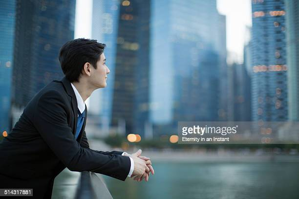 Young man looking up at city skyline.