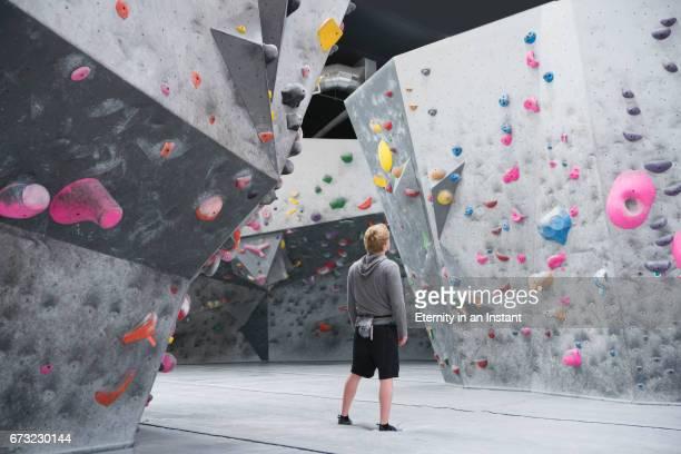 Young man looking up at climbing wall before climbing