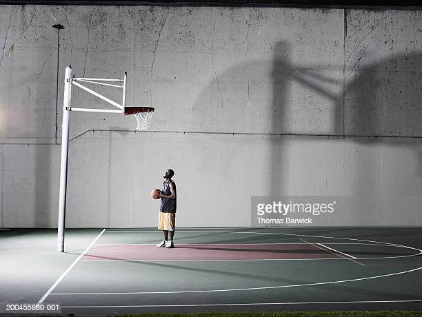 Young man looking up at hoop on outdoor basketball court, night