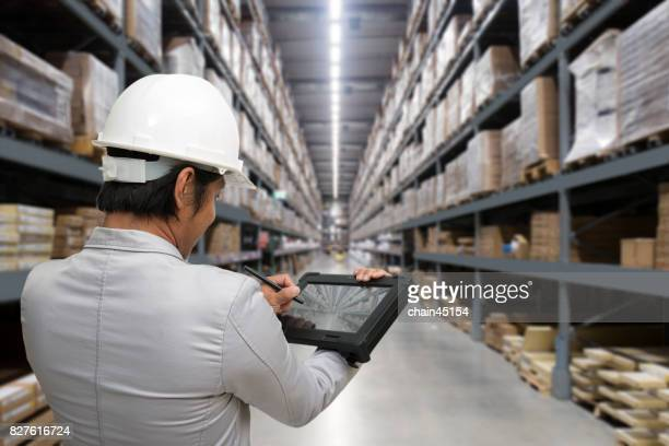 Young man looking up details on a tablet on the shops in a hardware warehouse for supplies , Business concept.