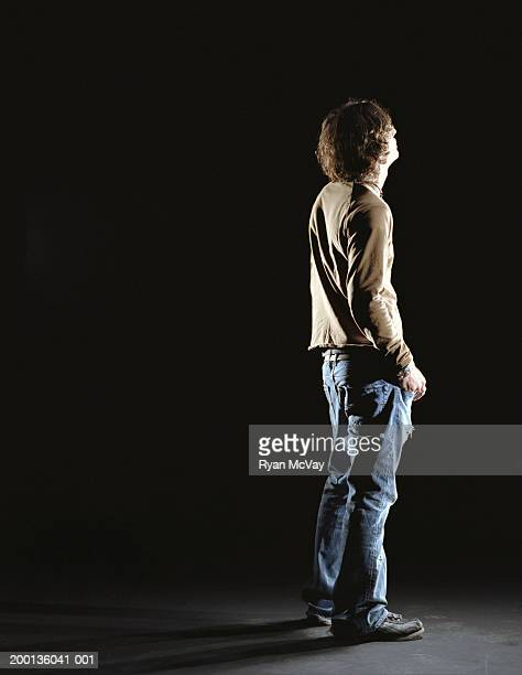 Young man looking up into darkness, rear view