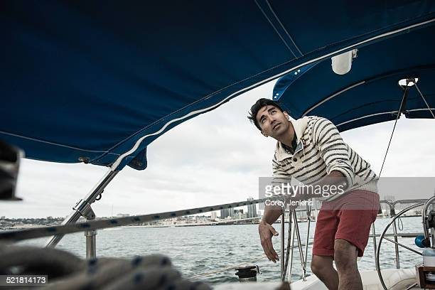 Young man looking up on sailing boat