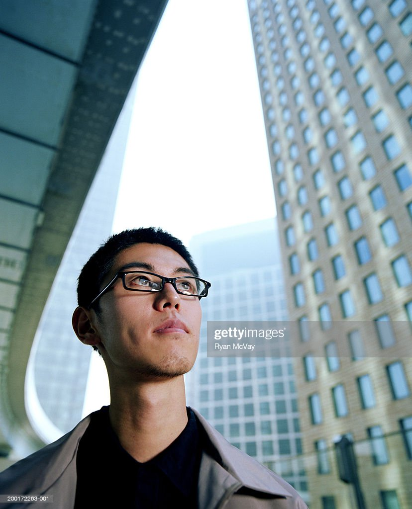 Young man looking up, skyscrapers in background : Stock Photo