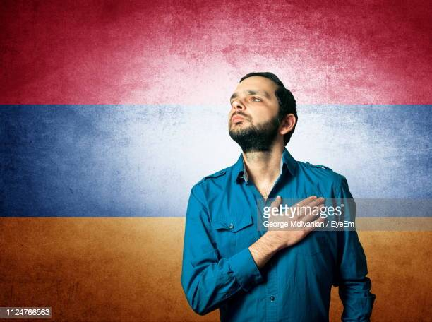 young man looking up while standing against armenian flag - armenian flag stock pictures, royalty-free photos & images