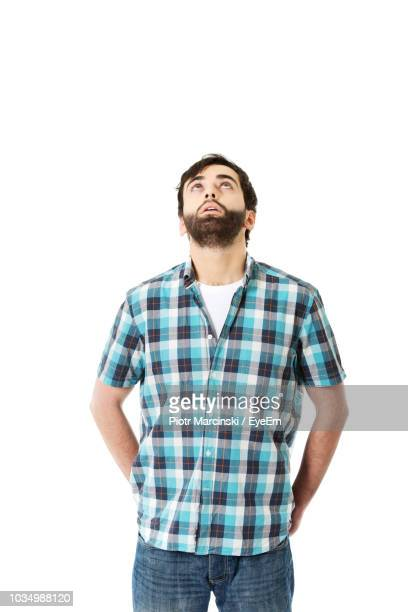 young man looking up while standing against white background - plaid shirt stock pictures, royalty-free photos & images