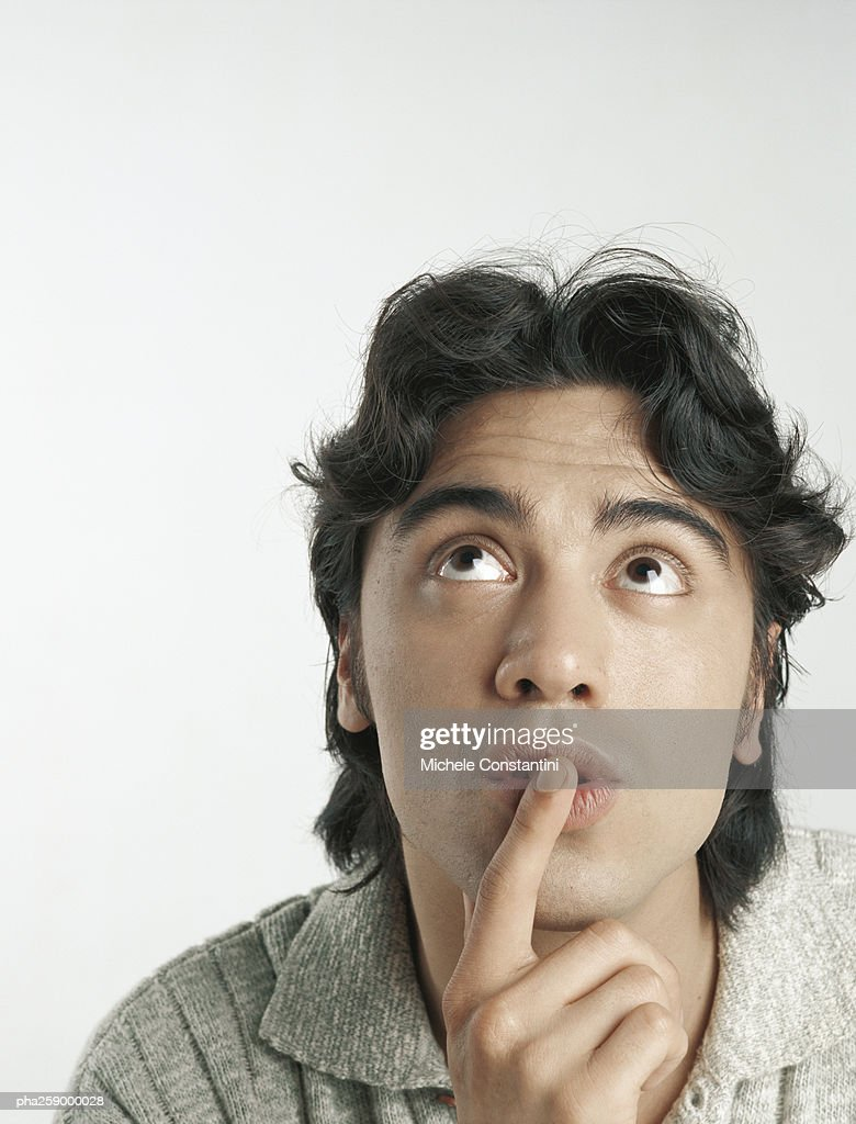 Young man looking up with finger on lips : Stockfoto
