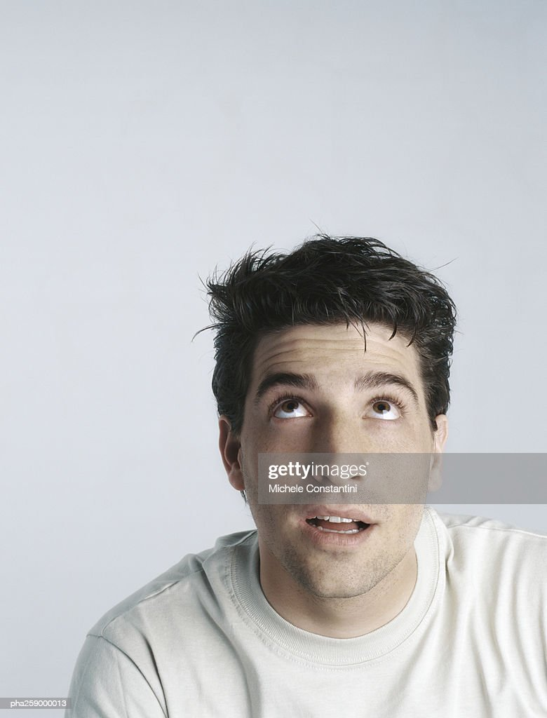Young man looking up with mouth slightly open, head and shoulders : Stockfoto