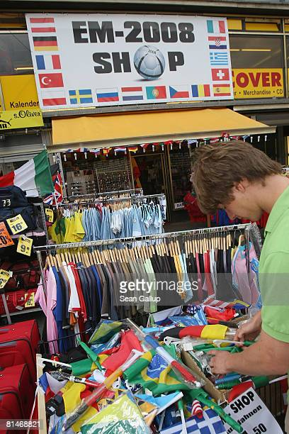 A young man looks among flags that can be attached to cars as ornaments at a shop selling tshirts flags and other merchandise related to the Euro...