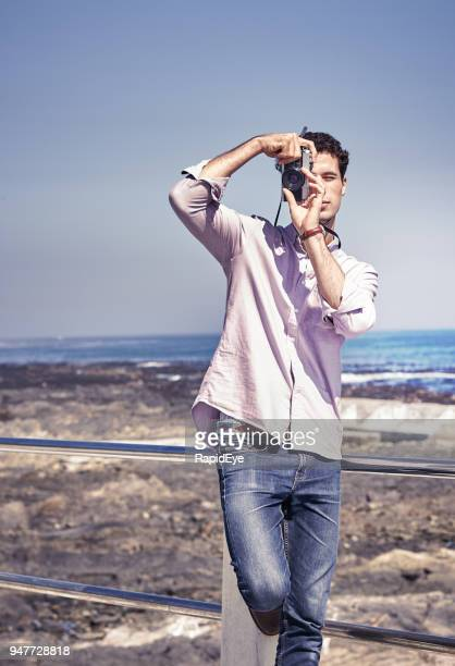 Young man looks at camera, taking photograph on seaside sidewalk