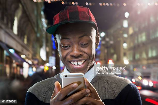 Young man looks at phone in urban street, smiling.