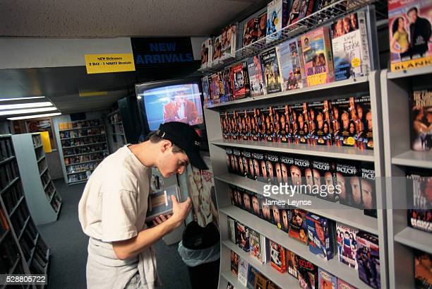 A young man looks at rental movies in Channel Video a video store in Manhattan New York