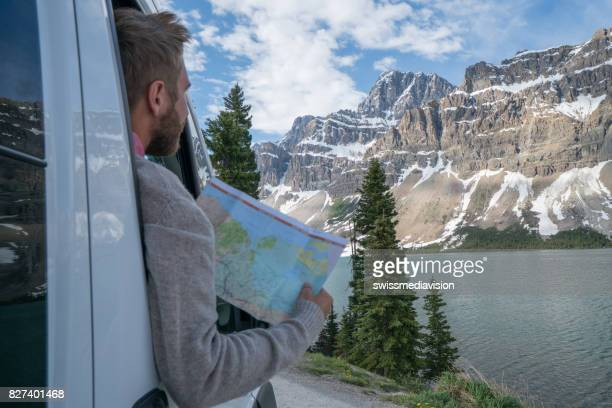 young man looks at road map near mountain lake - bow valley stock pictures, royalty-free photos & images