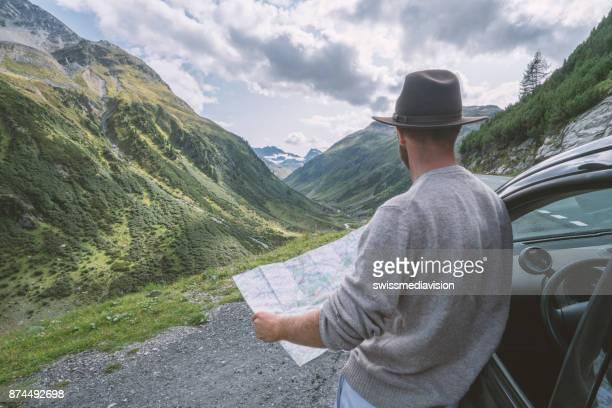 Jonge man kijkt naar de routekaart in de buurt van op bergweg, Zwitserland