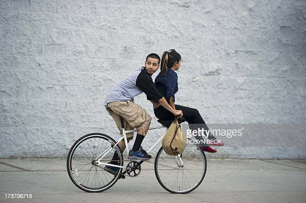 A young man looks back at protestors as he rides down the street with a girl on the handlebars in downtown Los Angeles July 16 2013 Protestors angry...