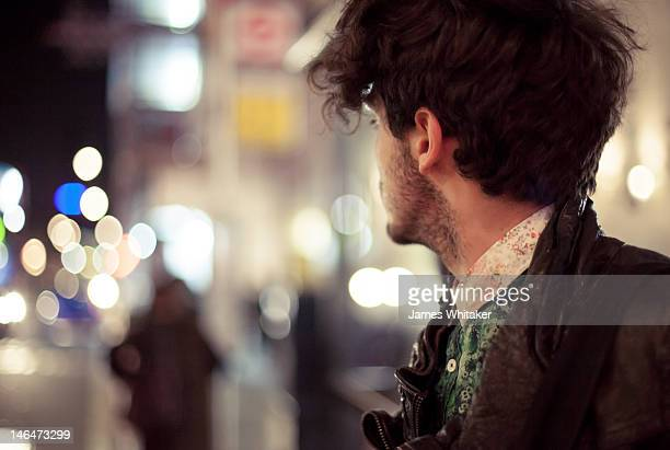Young man looks down road at night