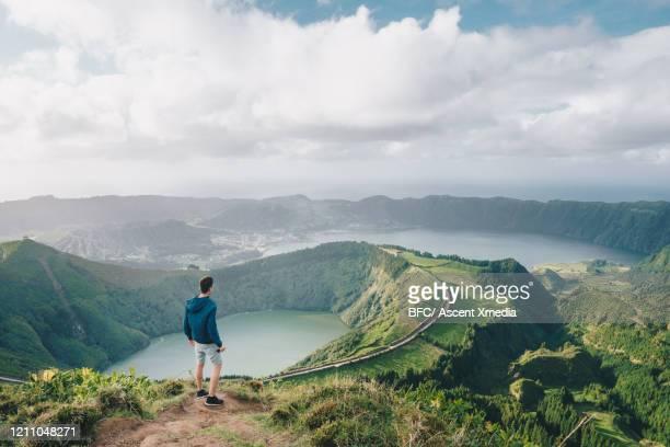 young man looks off from ridge crest - las azores fotografías e imágenes de stock