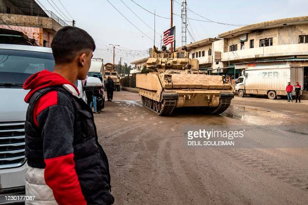 Young man looks on as US troops patrol in their military vehicles on the roads of the Syrian town of al-Jawadiyah and meet the inhabitants, in the...