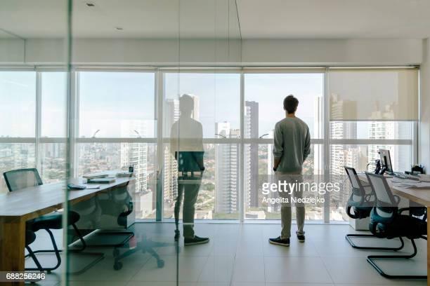 young man looks out of office window over city - dorsale foto e immagini stock