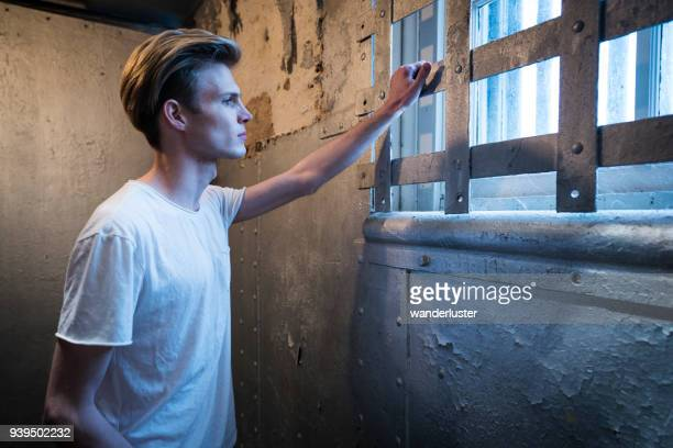 young man looks out prison window - child behind bars stock pictures, royalty-free photos & images