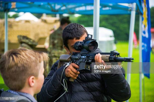 A young man looks through a Trijicon ACOG on a Lewis Machine and L129A1 tools during the event Stirling shows its support of the UK Armed Forces as...