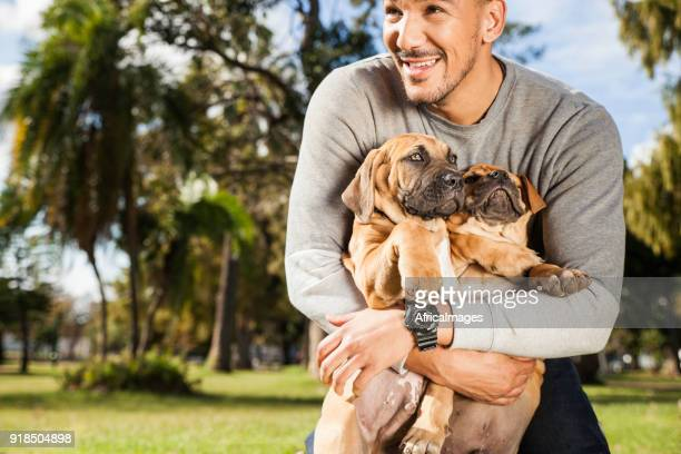 Young man loving his adorable puppies while playing at the park.
