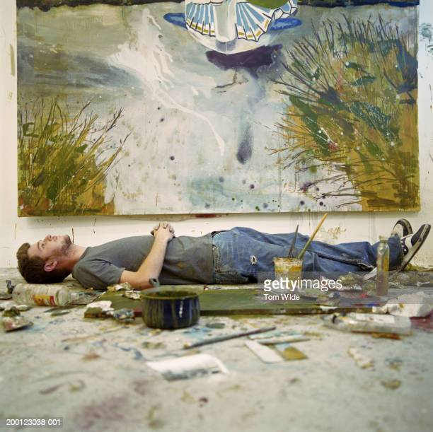 Young man lying amongst artists materials, painting in background
