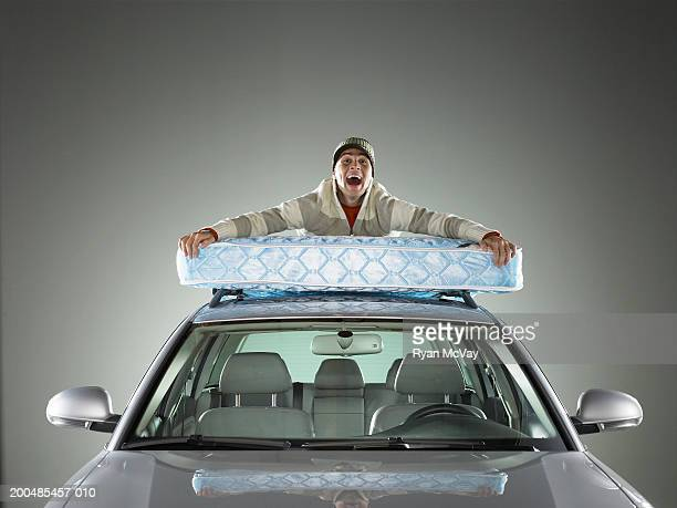 Young man lying atop mattress strapped to roof of car