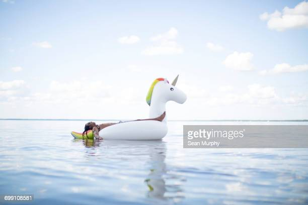 'Young man lying back on inflatable unicorn in sea, Santa Rosa Beach, Florida, USA'