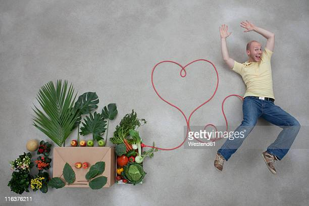 Young man lying by fruits and vegetables connected with electric cable