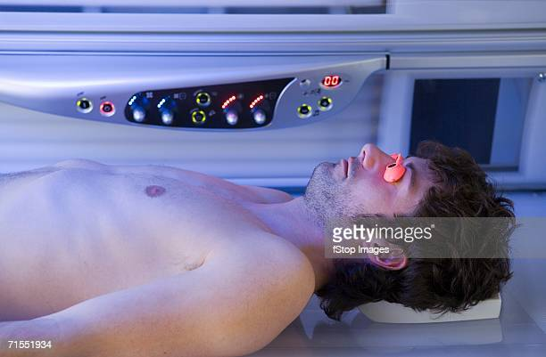 Young man lying down in a tanning bed