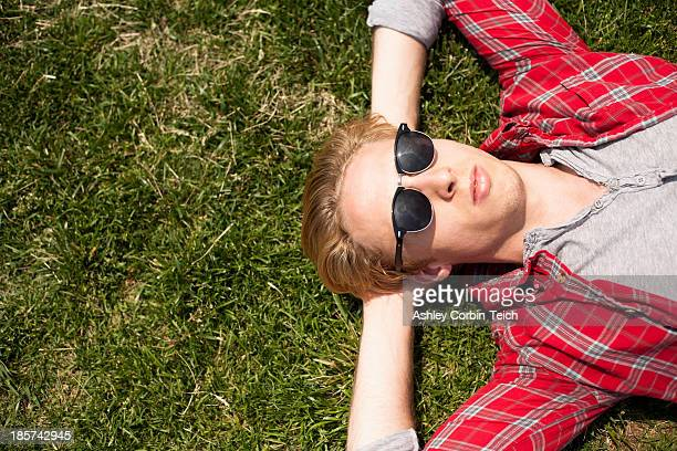 Young man lying down in park