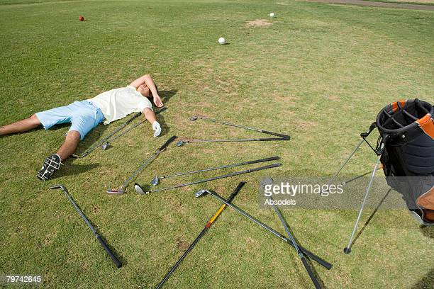young man lying down next to scattered clubs on golf course - lying down stock-fotos und bilder