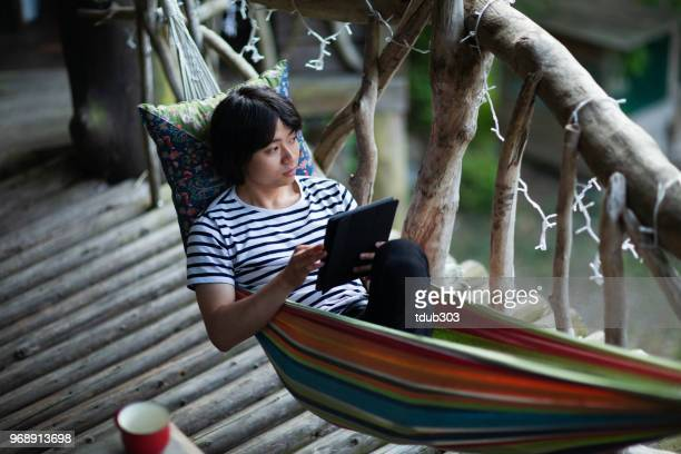 Young man lying in a hammock using a digital tablet computer