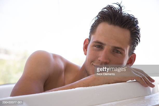 Young man lying in bath resting face on hand, smiling, portrait