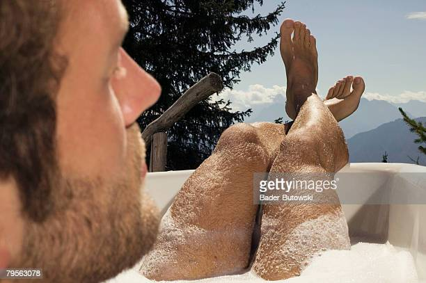 'Young man lying in bathtub, rear view, outdoors'