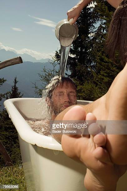 'Young man lying in bathtub, young woman pouring water on man?s head'