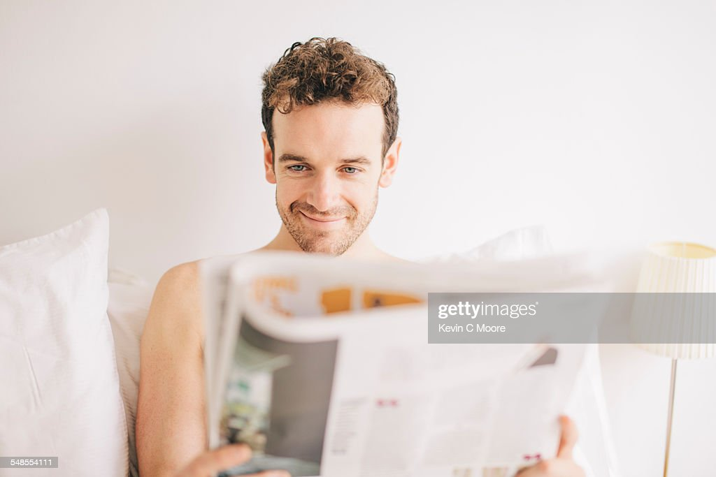Young man lying in bed smirking whilst reading newspaper : Stock Photo