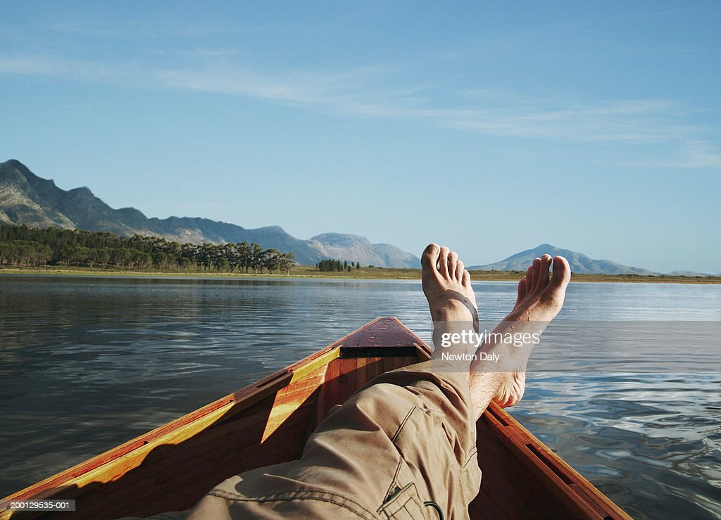 Young man lying in boat on lake, low section : Foto de stock