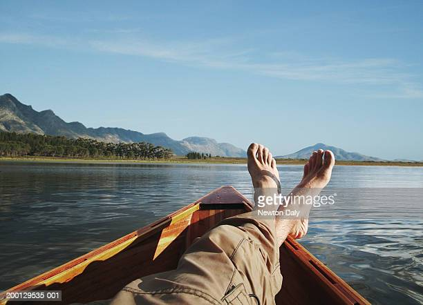 young man lying in boat on lake, low section - lazer imagens e fotografias de stock