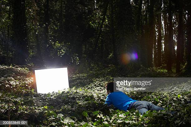 Young man lying in forest, watching monitor