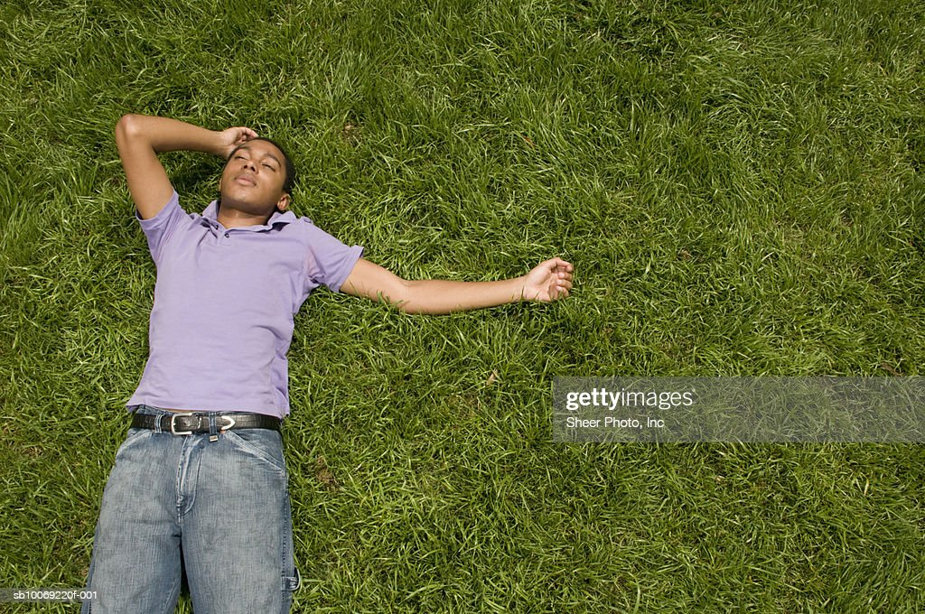Young man lying in grass, high angle view : Stockfoto